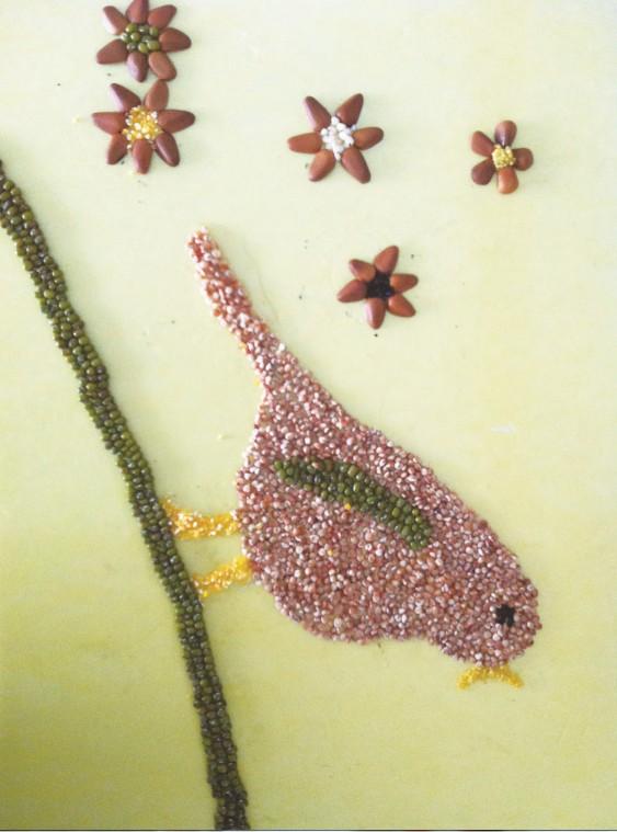2.用松子壳配合各色种子贴出花朵图案.        3.